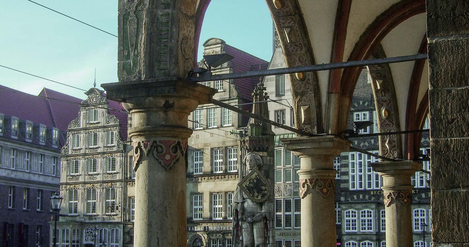 Blick aus den Rathausarkaden auf die Roland-Statue und die Häuserzeile im Hintergrund