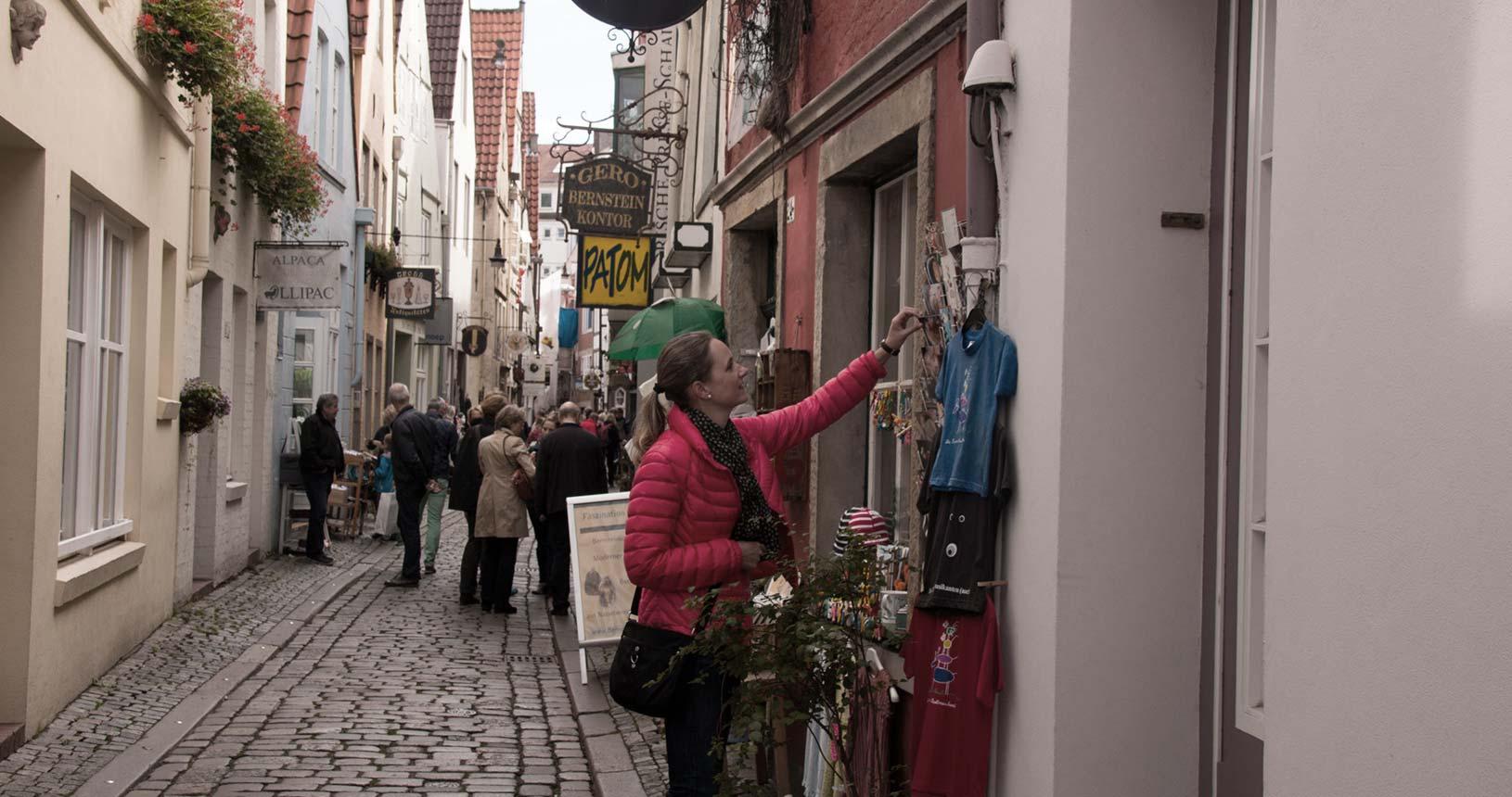 Menschen schlendern durch den Schnoor, Frau mustert Angebote eines Ladens